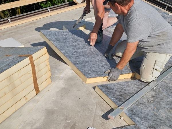 Pose d'un isolant sur la toiture plate